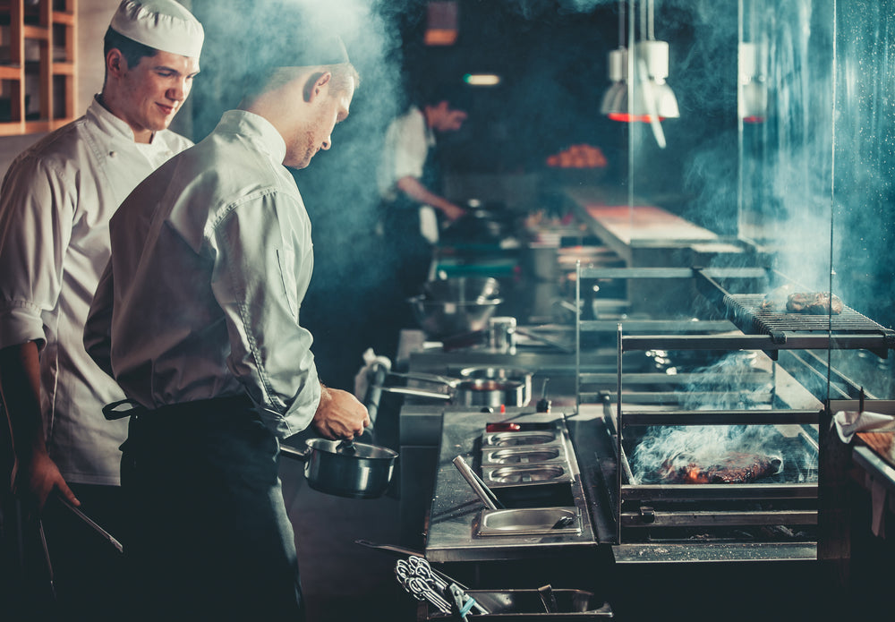 One chef holds a saucepan in a smoky kitchen as another chef watches on