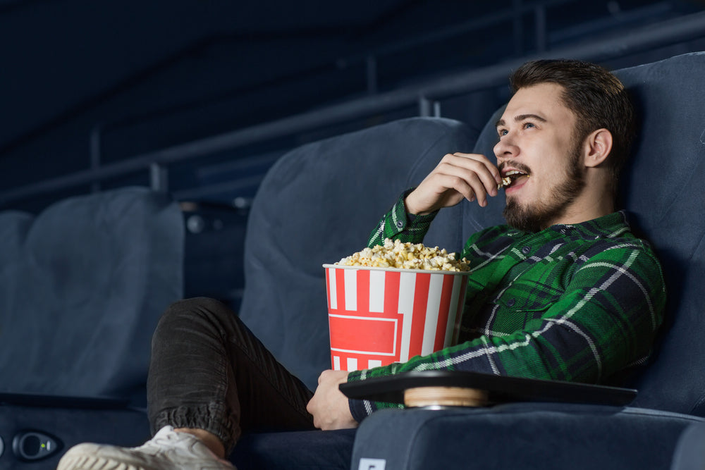 Bearded man wearing green checkered shirt smiles as he eats popcorn in a movie theatre