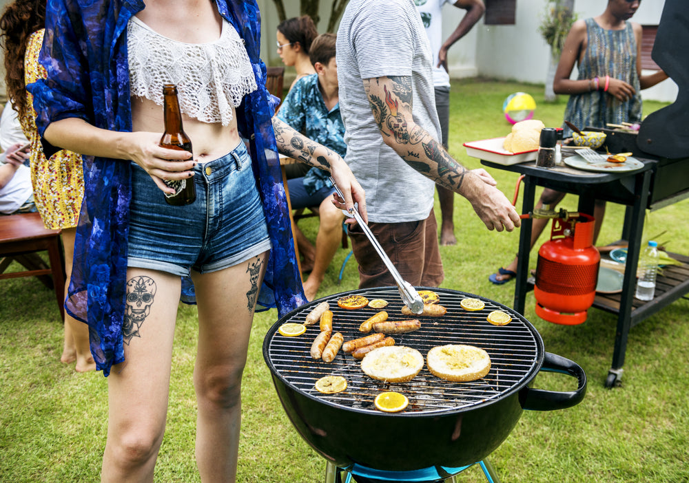 Diverse group of friends with tattoos at an outdoor bbq cookout