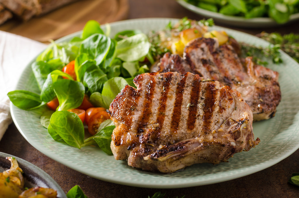 A plate of grilled pork chops with a side of salad on a wooden table