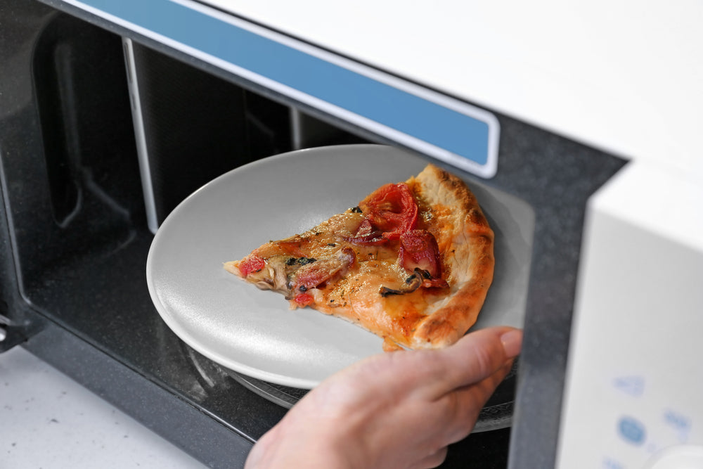 A hand placing a slice of pizza on a white plate inside a white microwave