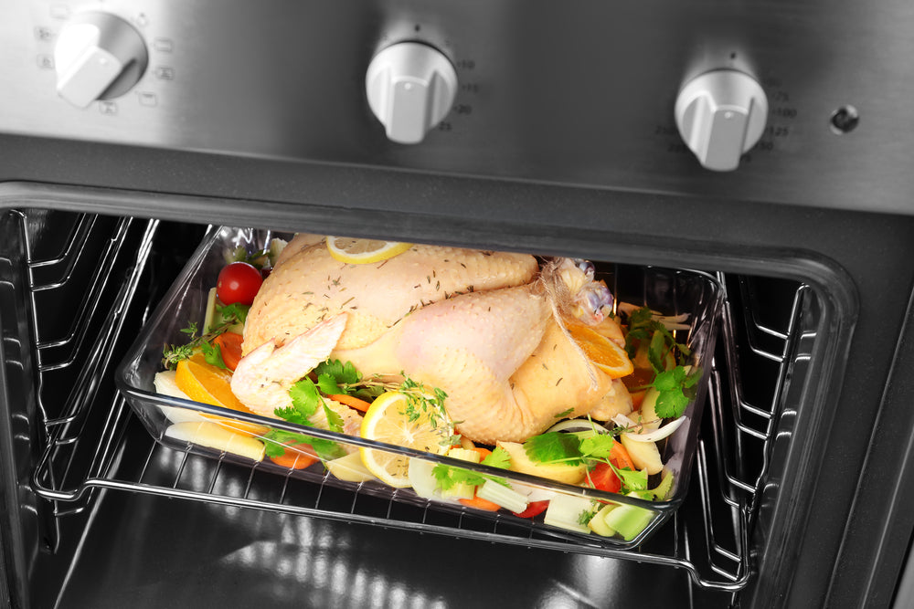 Casserole dish with whole raw turkey and other ingredients in oven