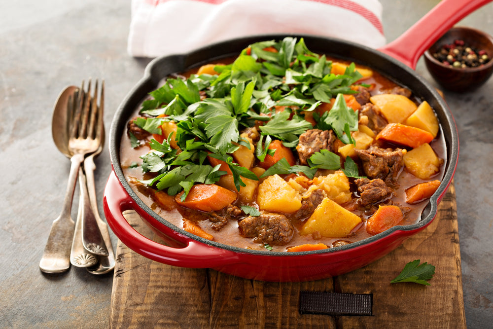 Traditional Irish Stew in a red skillet on a wooden cutting board next to a fork and spoon