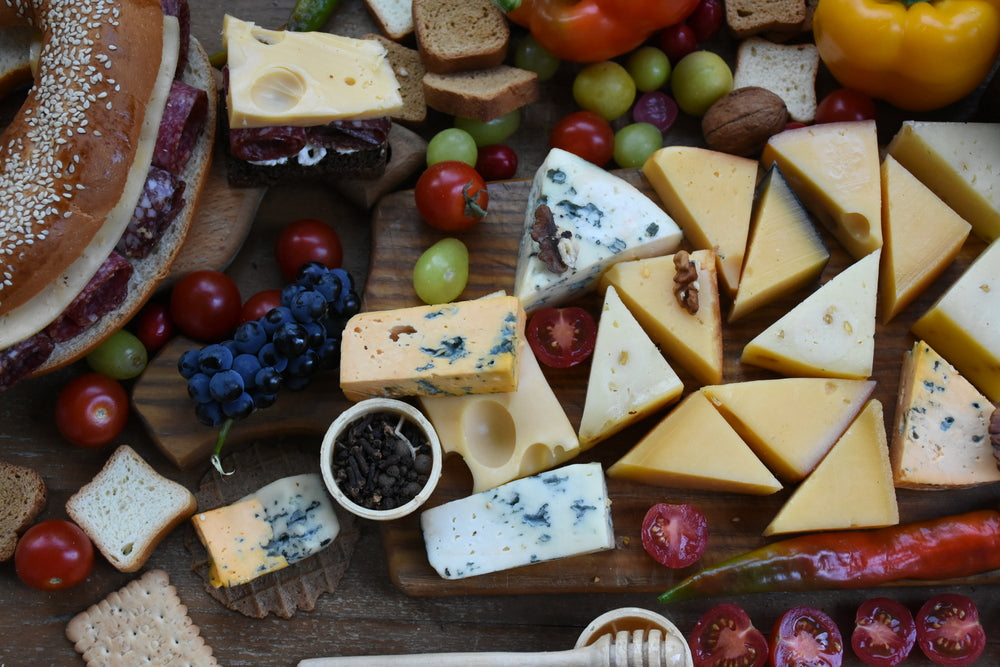 An arial shot of a large selection of cheese and meats and fruits on a wooden table