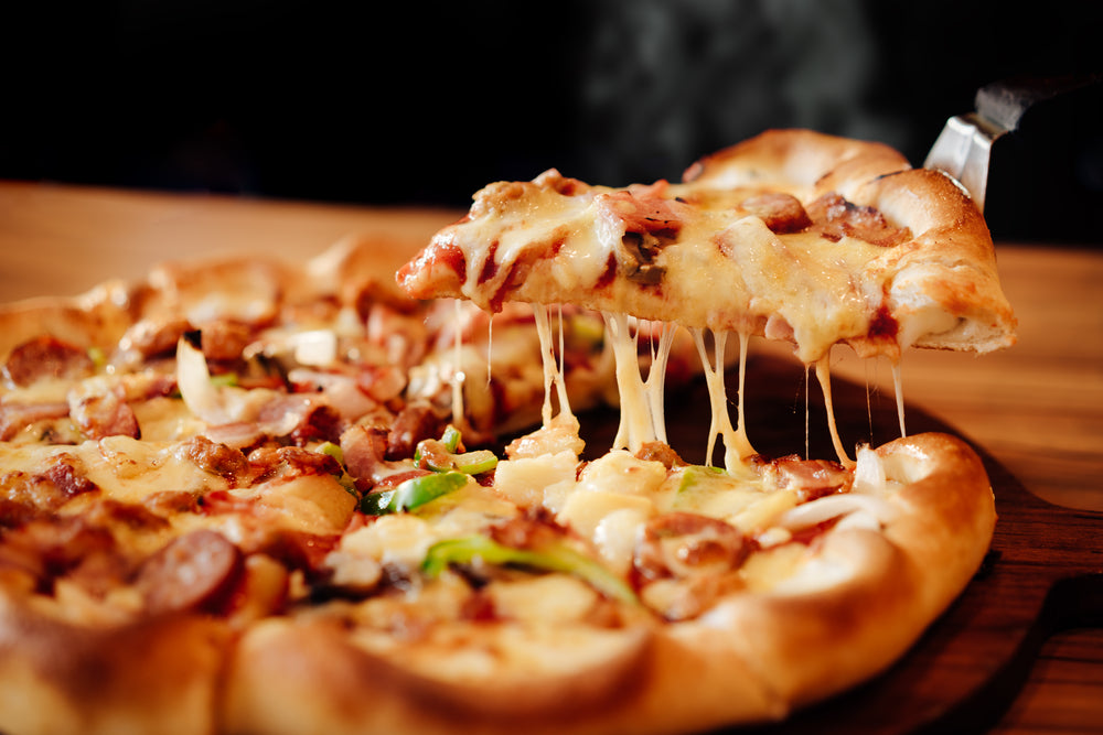 Cheesy slice being lifted from a freshly baked pizza on a wooden table