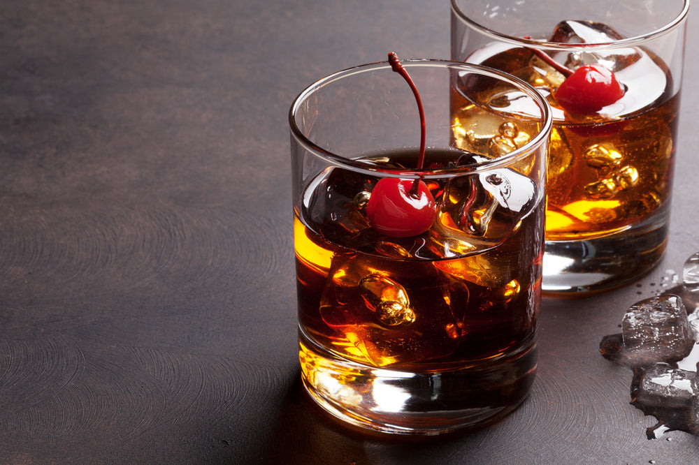 Manhattan cocktail with whiskey in two glasses with a cherry in each one against a dark surface