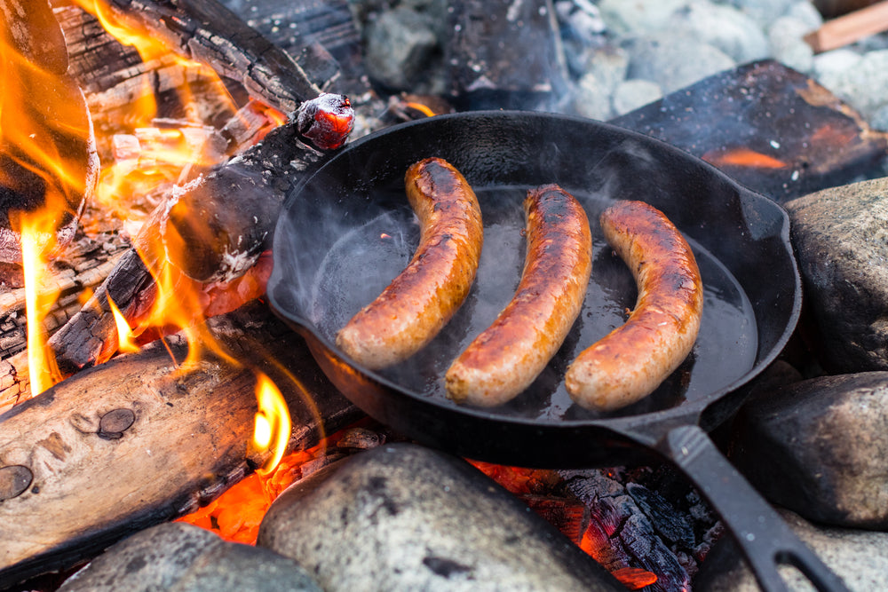 Live fire cooking juicy sausages over campfire.