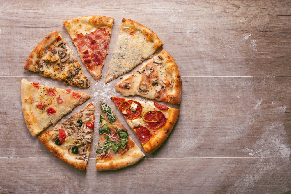 Eight slices of pizza with different toppings arranged into a circle on a wooden backdrop