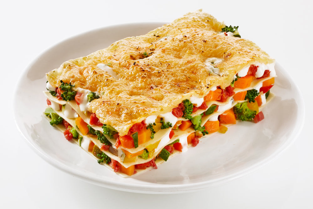 Healthy portion of fresh vegetable lasagne made with a mix of colorful fresh veggies served on a plate over a white background