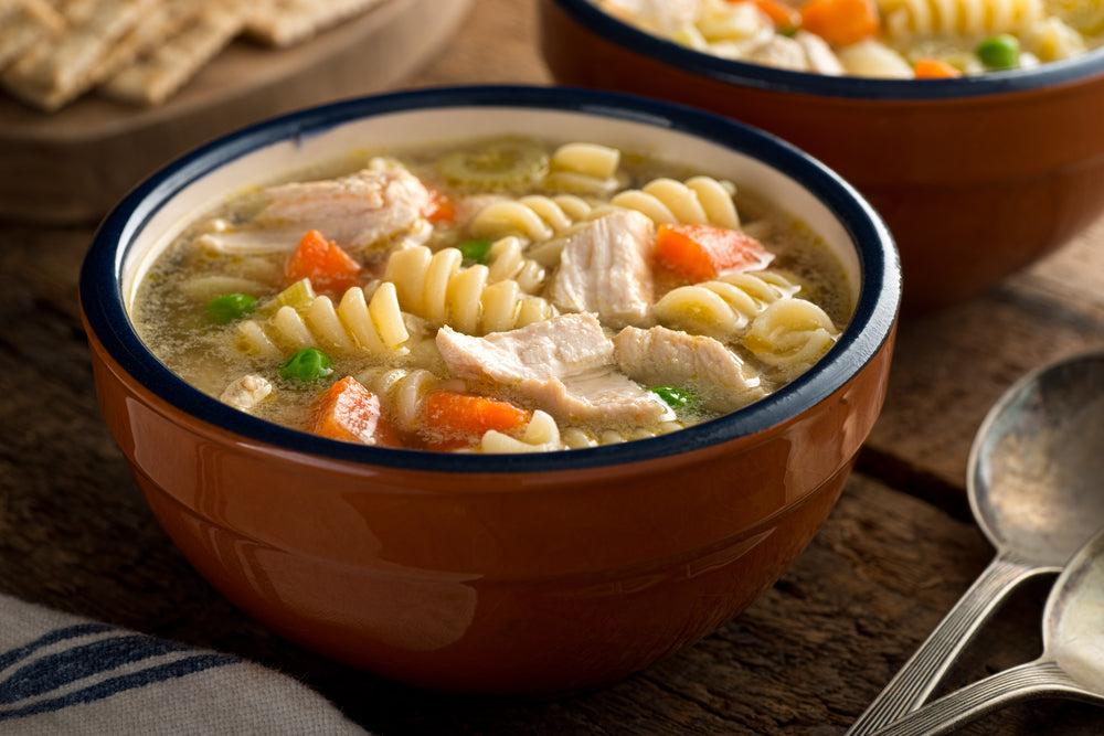 Brown bowl of chicken noodle soup next to two spoons with another bowl of soup in the background