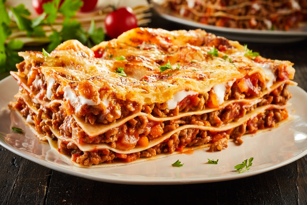 Portion of succulent ground beef lasagne topped with melted cheese and garnished with fresh parsley served on a plate in a close up view
