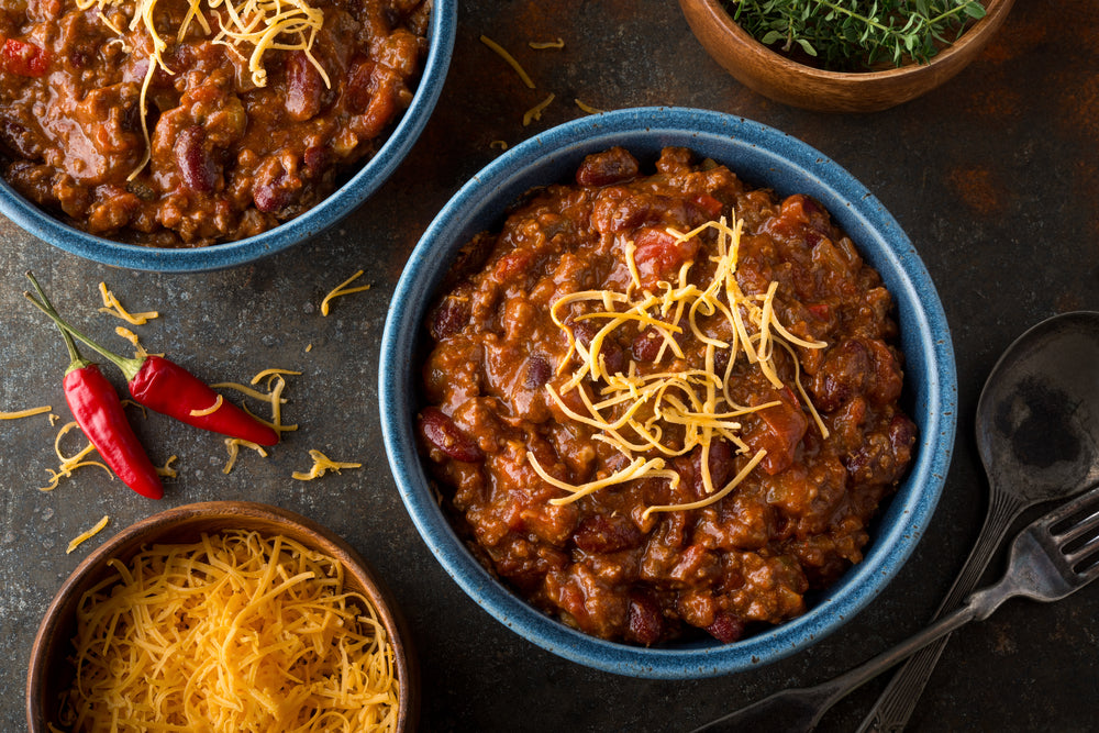 Bowls of chili with cheese on top next to a bowl of cheese and with peppers on the table