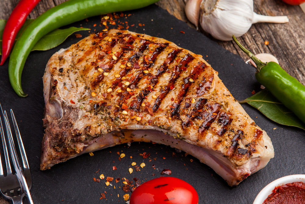 Grilled pork chop with seasonings and grilled tomatoes on a black background.