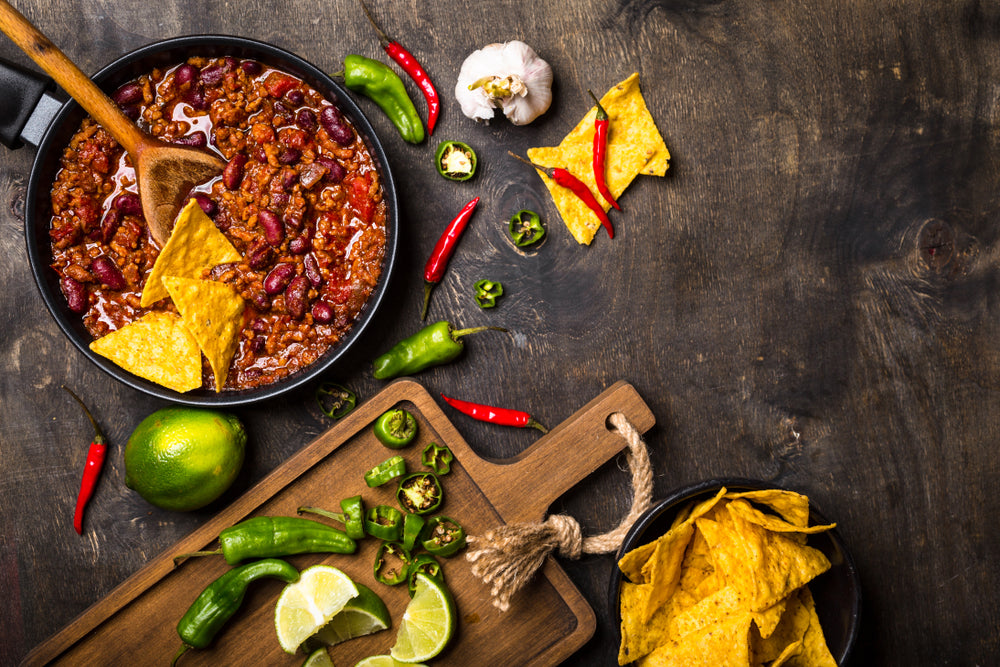 A large bowl of chili with a wooden spoon sticking out of it next to a cutting board with chopped limes and vegetables