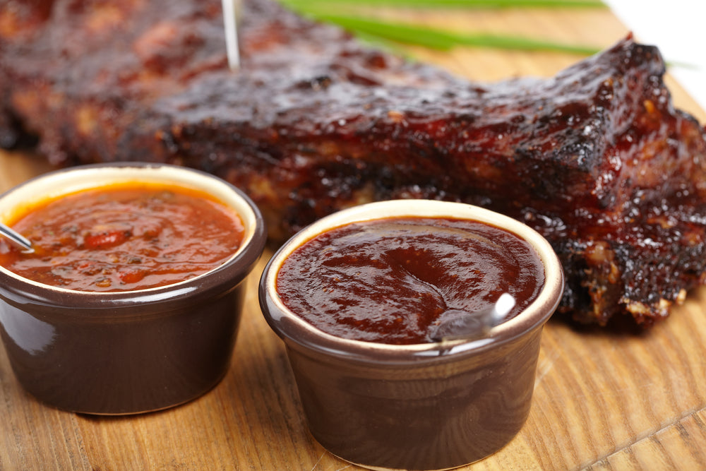 BBQ Ribs on a cutting board next to two small containers of different colored sauces