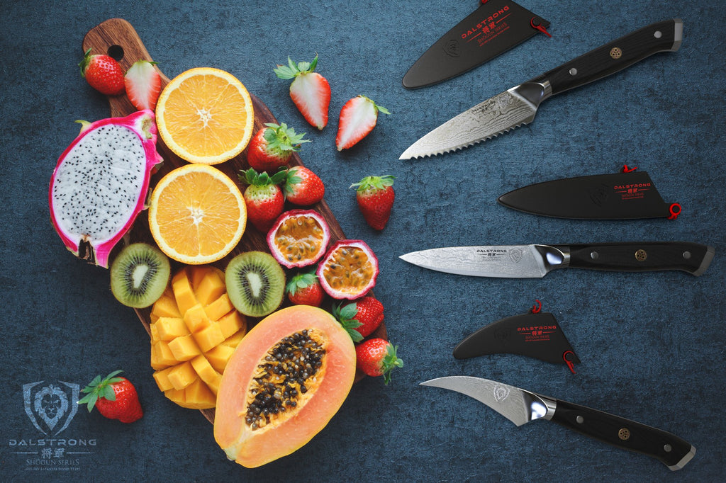 Three small paring knives on a blue surface facing several sliced fruits