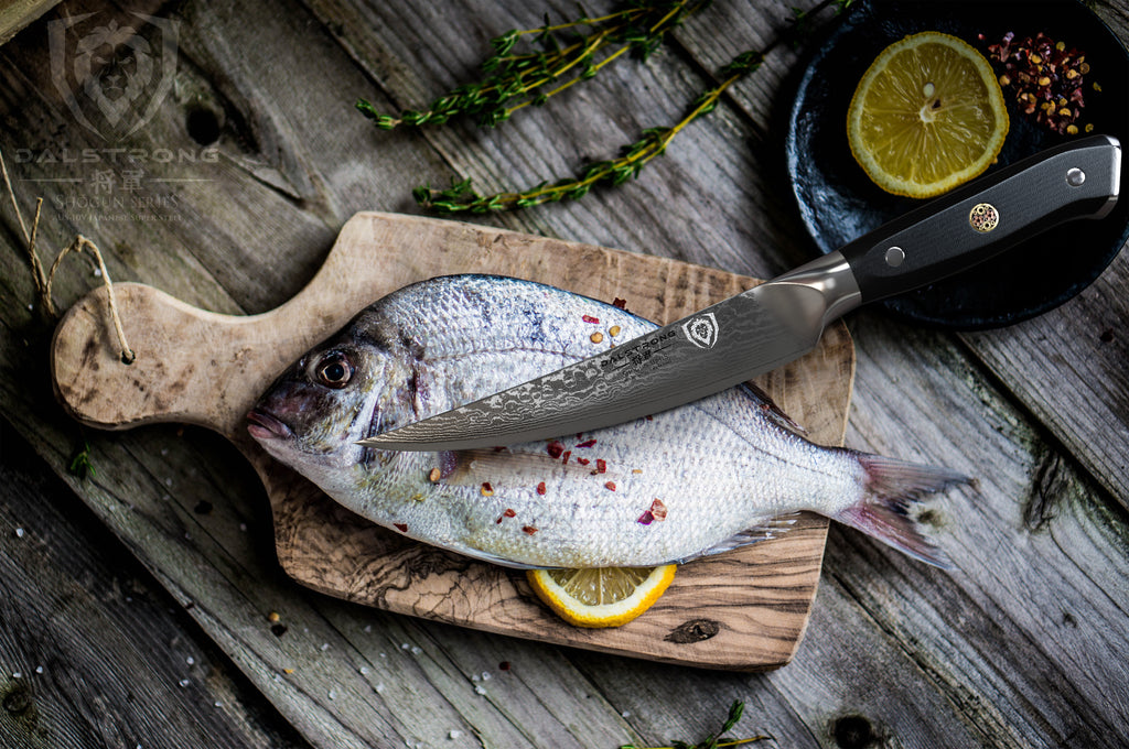Small fillet knife resting on an uncooked fish that is laying on a small wooden cutting board
