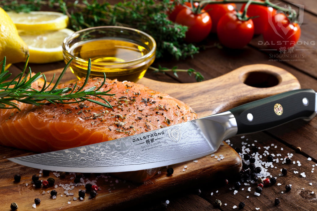 Filler knife rests on an uncooked salmon slice thats on a wooden cutting board surrounded by garnish