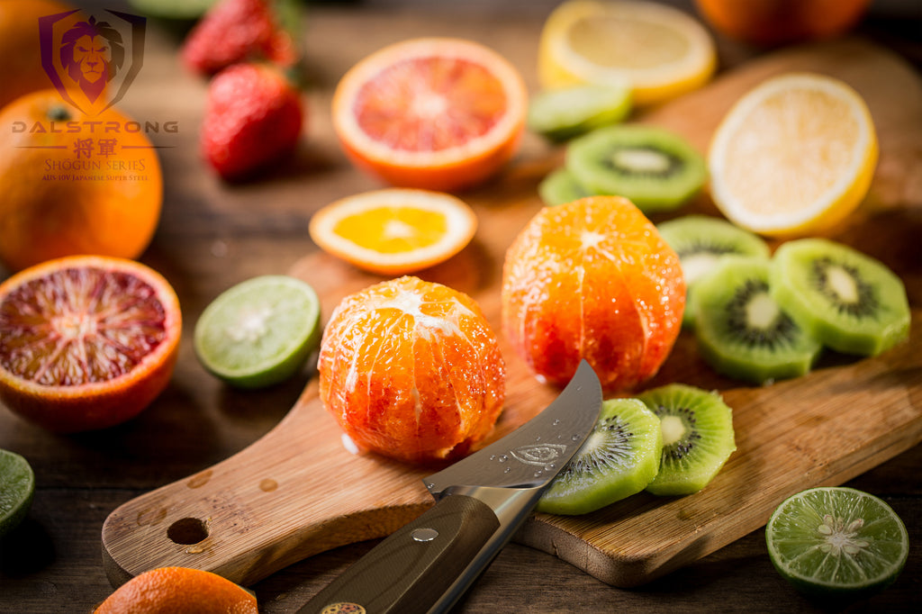 A small peeling paring knife surrounded by skinless fruit such as oranges and kiwis