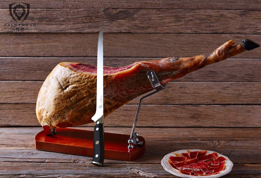 A stylish slicing knife balances on a leg of pork that is presented on a stand