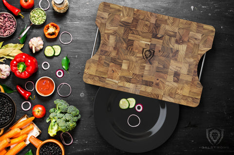 Dalstrong Teak Cutting board on wooden surface surrounded by vegetables