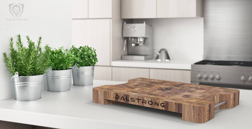 A clean white home kitchen with small potted plants and a large wooden cutting board in the foreground