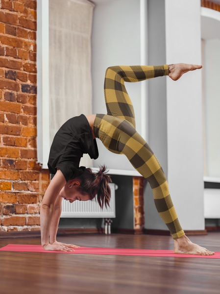 yogi model in a yoga pose wearing  yellow and black buffalo plaid print leggings yoga pants