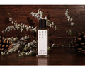 Arborist by Jorum Studio staged photo with pinecones and white flowers at AVÉ PARFUM