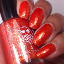 nail polish by crystal knockout, carnelian meld, red orange jelly with gold flakes and shimmer