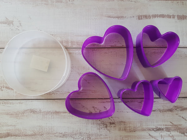 Plastic cookie cutters in a container, Heart