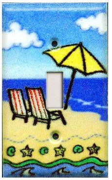 A handmade single toggle fused glass switch plate with the image of a beach scene.
