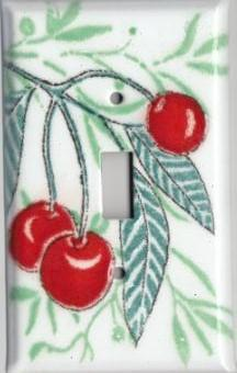 A handmade single toggle fused glass switch plate cover with the image of cherries.