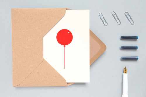 Foil blocked balloon card by Ola.  A vivid red balloon presented with perfect simplicity on a stone background.  Traditionally foil blocked on quality textured paper.  Made in the UK  270gsm paper stock  Kraft paper envelope  A6 size  Left blank inside for your own message