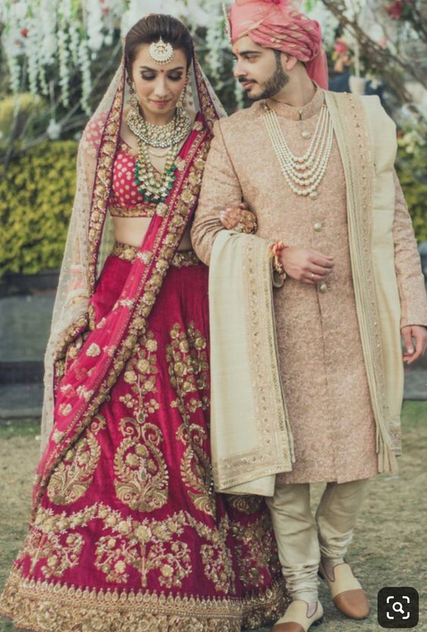 Luxurious Bridel Groom Dress In Red Lahnga Choli And Pinkish Sherwani.Bridal Lahnga Choli Embalished With Pure Dabka,Zari,Nagh,And, Threads Work.Groom Sherwani Based On Pure Jamawar Fabric In Light Pinkish Color.Sharwani Work On Gala And Sleeves With Dabka And Nagh Work.It Is Complete Packeg Of Bride And Groom Outfit.