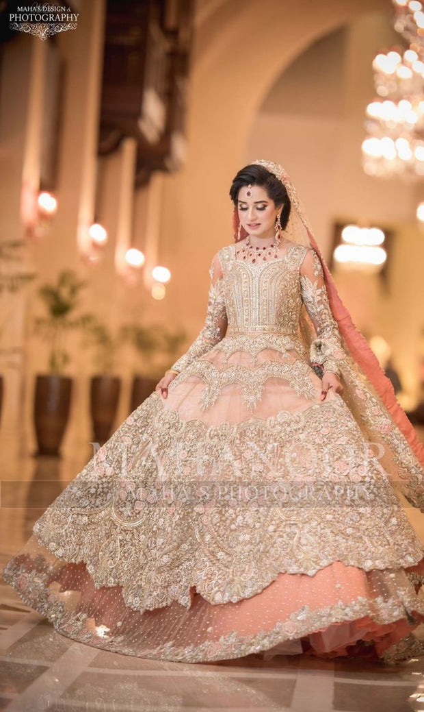 Walima Bridal Dress In Beutifull Peachy Pink Color.Work Embalishment With Pure Dull Gold And Silver Dabka,Nagh,Zari Pearls,Stones,Crystal And Dhaga Flower Work.Beutifull Dress Can Custumized In Any Color.Fabric Can B Change As Per Customer Drsiring Fabric.