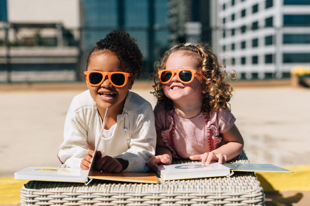 two little girls reading laughing in downtown Los Angeles on a rooftop with sunglassed
