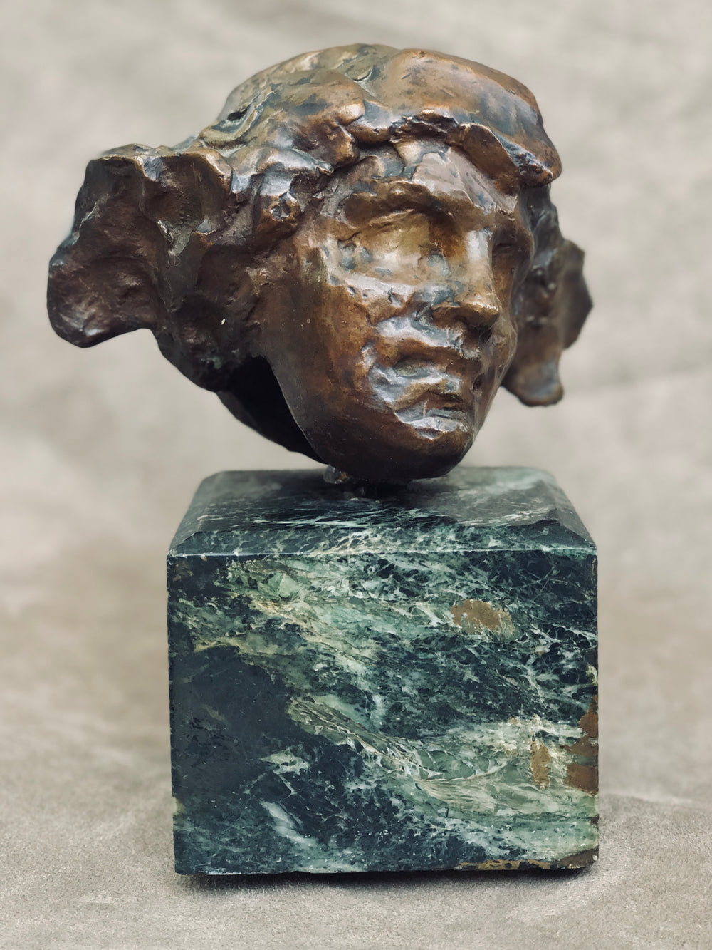 An Art Deco bronze head mounted on a marble pedestal signed N. Giordano