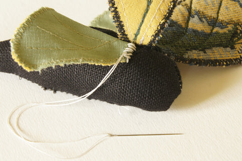 right underwing sewn to the right side of the body with a whipstitch in light thread, so as to be visible for the demonstation