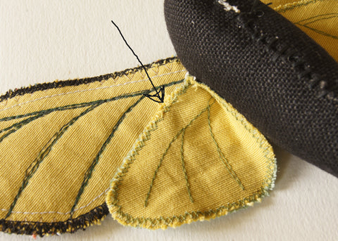 underside of wings, with arrow pointing to whipstitches which join the lower wing to the upper wing
