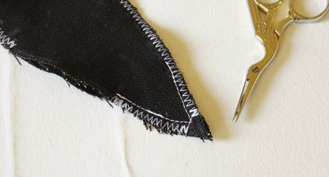 reinforce stitching along the V at the end of the body, then zigzag stitch seams to finish
