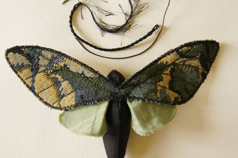 top view of moth with a piece each of cotton cord, braided cord and feather trim as choices for antennae