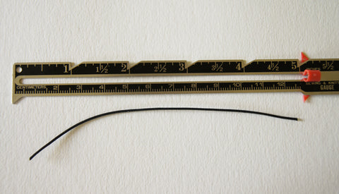 seam gauge on surface with a 5 inch length of cotton cord