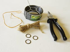 phot of a coil of wire, a skein of hemp cord, three small metal rings and one pair wire clippers