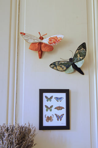 two finished moths hanging from nails on the wall, just above a print of butterflies and a large vase of lavender