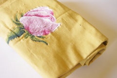 a rolled piece of yellow canvas upholstry fabric (cotton) with a machine embroidered rose in the center.