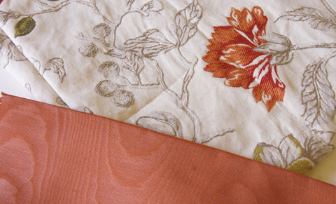 cream upholstery brocade with orange flowers next to a small piece of orange satin