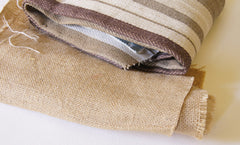 a rolled up piece of natural colored burlap, next to a folded piece of beige and brown striped canvas fabric.