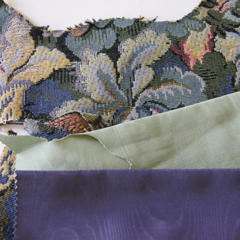 blue tapestry fabric next to remnants of dark blue and light green satin