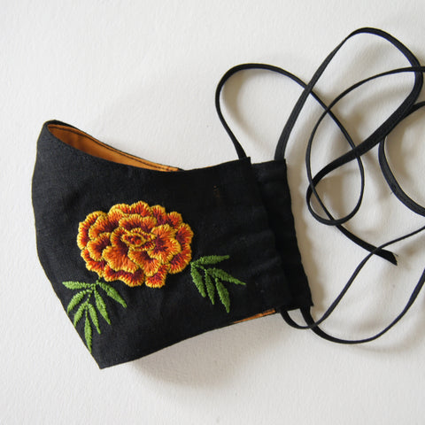 black linen mask with orange lining and marigold embroidery on the left side