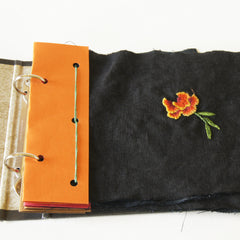 two ring binder open to show orange header sewn to marigold embroidery sampler
